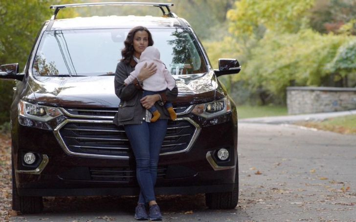 Athena Karkanis holding a baby in her car.