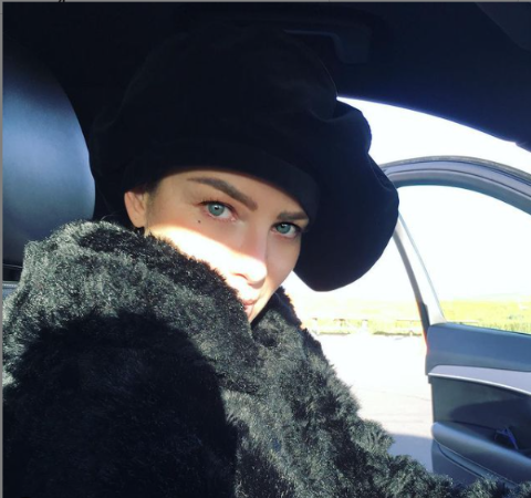 Lauren German wearing a black coat and a hat in her car